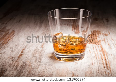 glass of whiskey over wooden background - stock photo