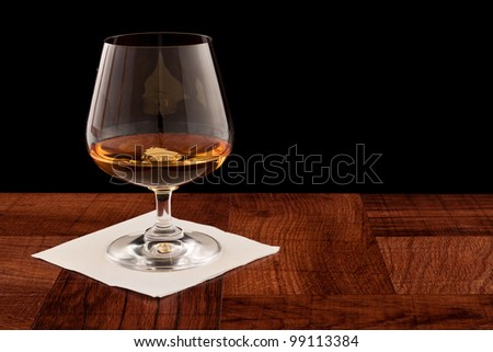 glass of whiskey served on a bar top isolated on a black background - stock photo