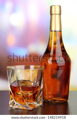 Glass of whiskey with bottle, on dark background - stock photo