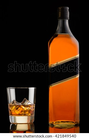 Glass of whiskey with ice and bottle on black background. Whisky on rocks - stock photo