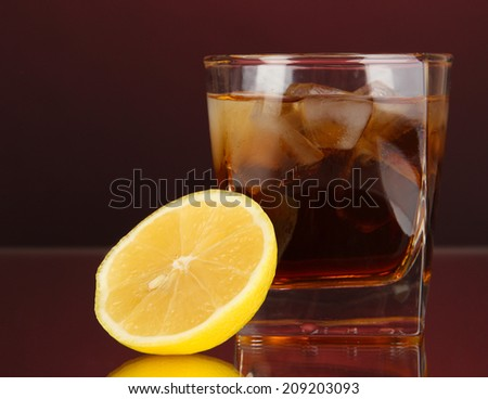 Glass of whiskey with ice and lemon on red background