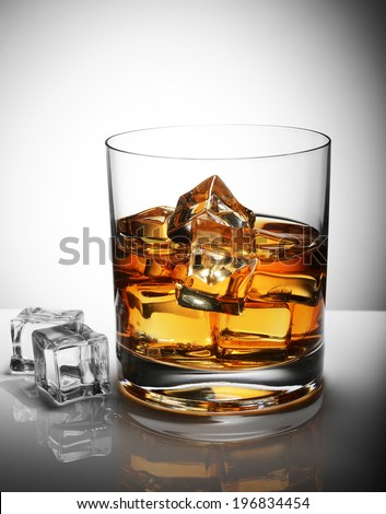 glass of whiskey with ice cubes - stock photo