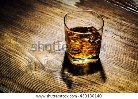 glass of whiskey with ice cubes on wood table - stock photo
