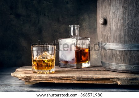 Glass of whiskey with ice decanter and barrel on wooden table - stock photo
