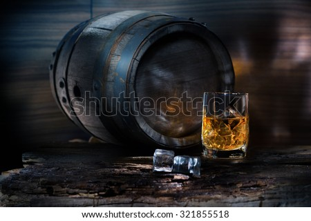 glass of whiskey with ice near the vintage barrels