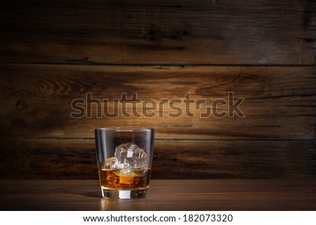 glass of whiskey with ice on a wooden background - stock photo