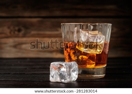 Glass of whiskey with ice on a wooden background. Copyspace on the left. - stock photo