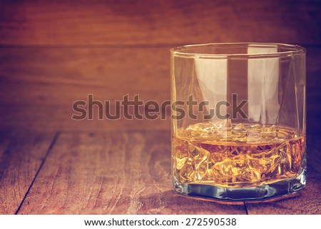 glass of whiskey with ice on a wooden background made with vintage tones - stock photo
