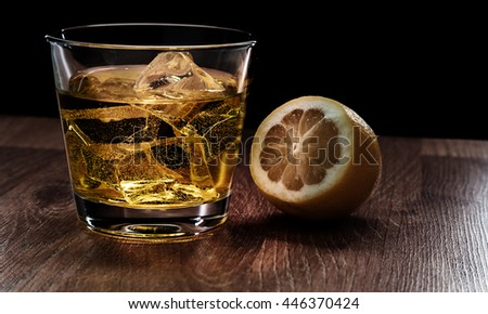 Glass of whiskey with ice on a wooden table - stock photo