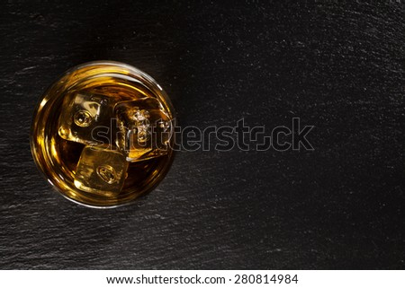Glass of whiskey with ice on black stone table. Top view with copy space - stock photo