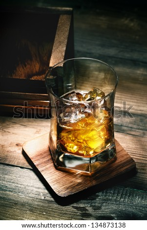 Glass of whiskey with ice on wooden lining and planking texture - stock photo
