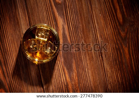 Glass of whiskey with ice on wooden table background. Top view with copy space - stock photo