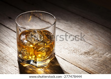 Glass of whiskey with ice on wooden table background with copy space - stock photo
