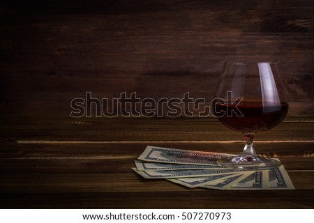 Glass of whiskey with money on a wooden table.