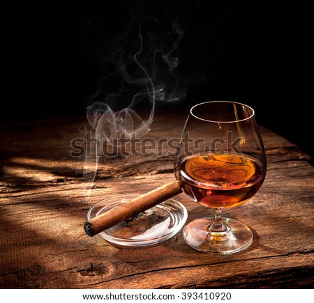Glass of whiskey with smoking cigar and ice cubes on wooden table - stock photo