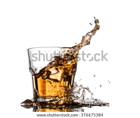 Glass of whiskey with splash, isolated on white background - stock photo