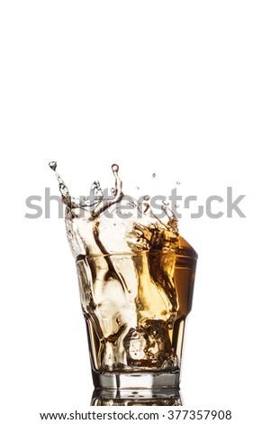 Glass of whiskey with splash, isolated on white background. - stock photo