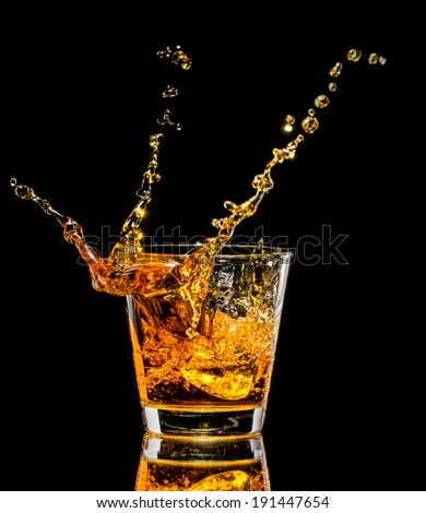 Glass of whiskey with splash on black background - stock photo