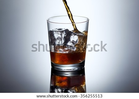 Glass of whiskey with splash, selective focus on the glass