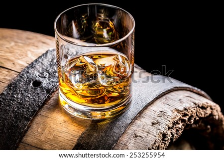 Glass of whisky and old wooden barrel - stock photo