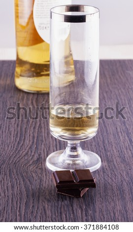 Glass of whisky near two blocks of chocolate over table, vertical image - stock photo