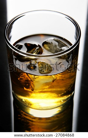 Glass of whisky with ice close up - stock photo
