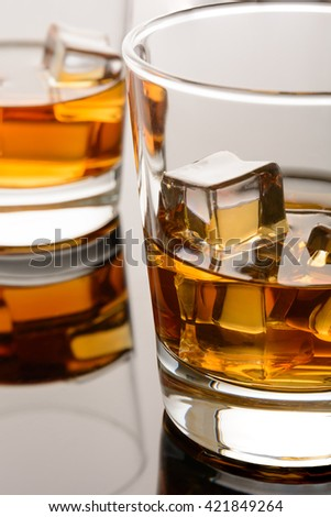 Glass of whisky with ice cubes. Whiskey on the rocks. Macro - stock photo