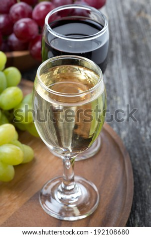 glass of white and red wine, fresh grapes on a wooden board, vertical