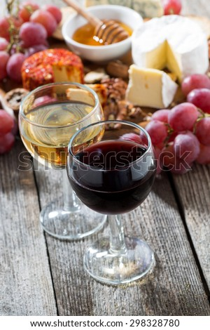 glass of white and red wines, appetizers on a wooden background, vertical, top view - stock photo