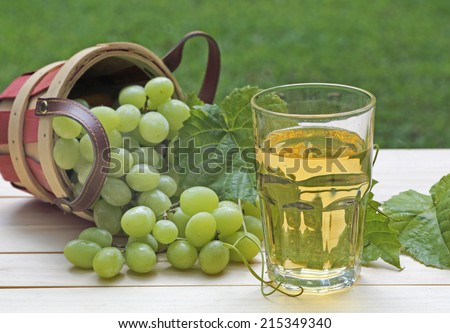 Glass of white grape juice and grapes outside on a table - stock photo