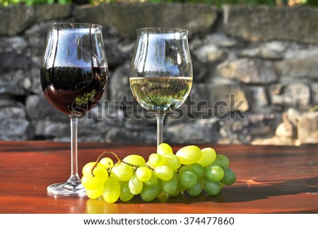 Glass of white wine and a bunch of grapes. Lavaux region, Switzerland - stock photo