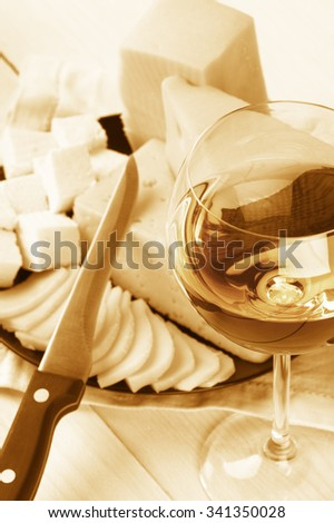 Glass of white wine and assorted cheese on rustic wooden table. Monochrome toned image. Shallow DOF, focus on wine. - stock photo