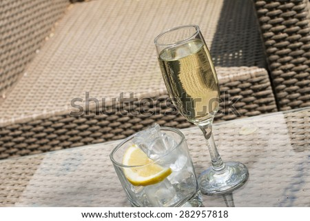 Glass Of White Wine And Glass With Ice And Lemon - stock photo