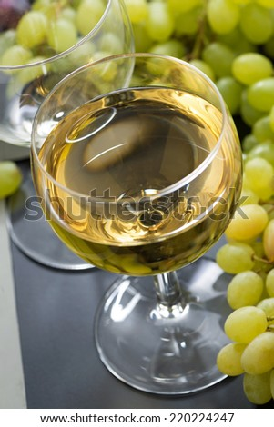 glass of white wine and grapes, close-up, vertical