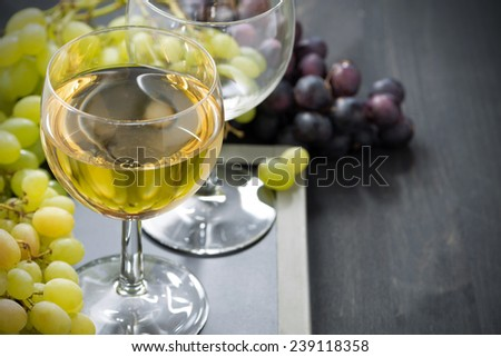 glass of white wine and grapes on a blackboard, horizontal, top view, close-up - stock photo