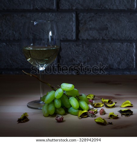 glass of white wine and grapes on wooden table, gray bricks background - stock photo