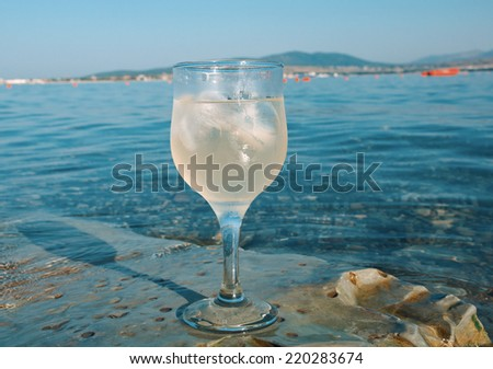 Glass of white wine by the coast.on the rocks, washed by the waves of the sea - stock photo