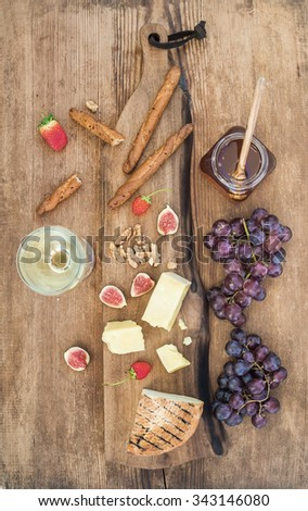 Glass of white wine, cheese board, grapes, figs, strawberries, honey and bread sticks on rustic wooden background, top view - stock photo