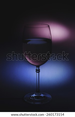 Glass of white wine in soft subdued light with unusual light effects and sensitive atmosphere