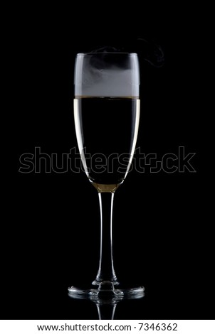 Glass of white wine isolated over black background, with smoke