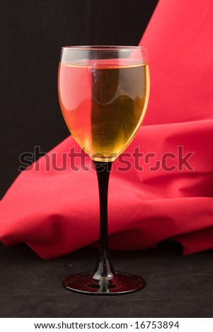 Glass of white wine  on a red and black background