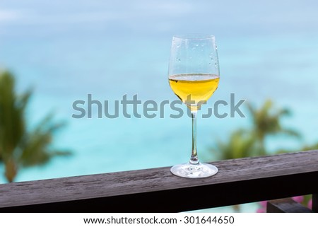 Glass of white wine on balcony rail, Tropical view