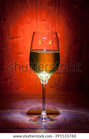 Glass of white wine on red old wooden background with place for text - stock photo