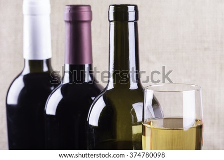 glass of white wine on the background bottles - stock photo