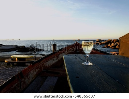 glass of white wine on the old boat table in a cafe on the beach at sunset, selective focus