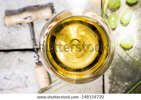 Glass of white wine on top of the background of stone, corkscrew and cork, vine leaves and grapes. - stock photo