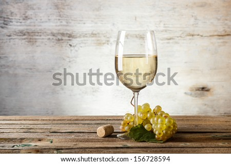 Glass of white wine on vintage wooden table - stock photo