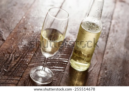 Glass of white wine on wooden table. - stock photo