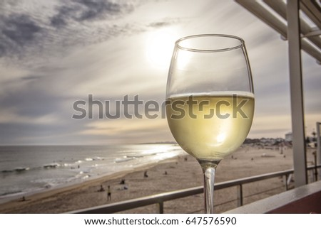 Glass of white wine overlooking the beach with sunset