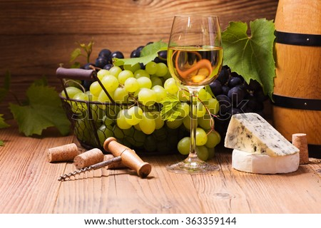 Glass of white wine, served with grapes and cheese on a wooden background - stock photo
